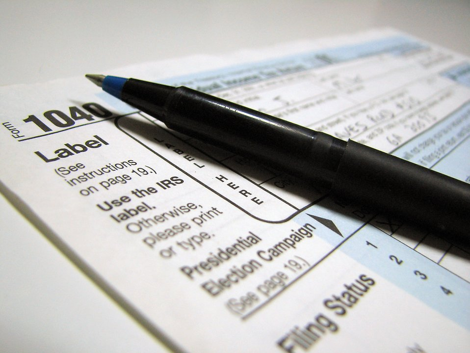 Closeup of a 1040 tax form and a pen on a white background.
