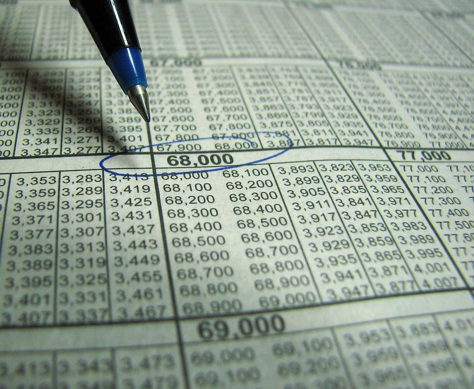 Closeup of a tax income chart and a blue pen circling a number.