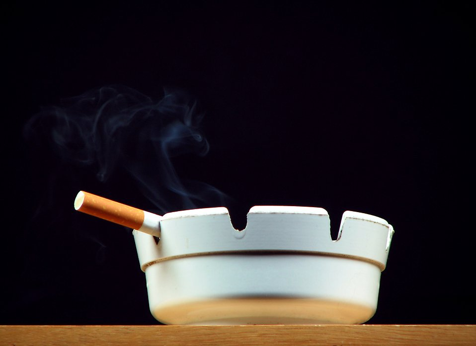 A cigarette burning in a white ashtray : Free Stock Photo
