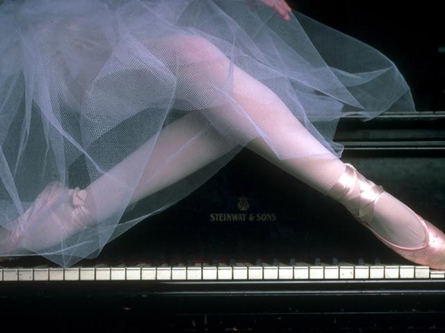 Closeup of a ballerina's legs posing on a piano : Free Stock Photo