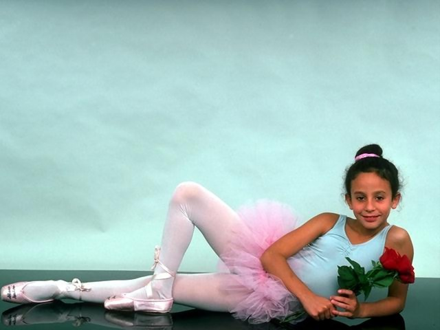 A teen ballerina posing on the floor with a rose : Free Stock Photo