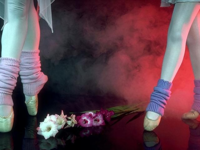 Closeup of legs and slippers of two ballerinas with flowers and smoke.