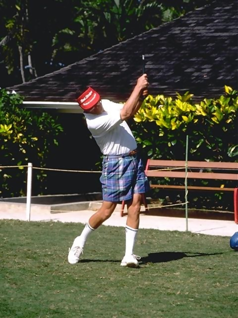 An older man in shorts swinging a golf club : Free Stock Photo