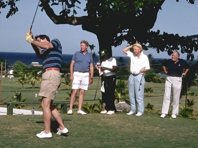 A group of men playing golf on a course by the ocean.