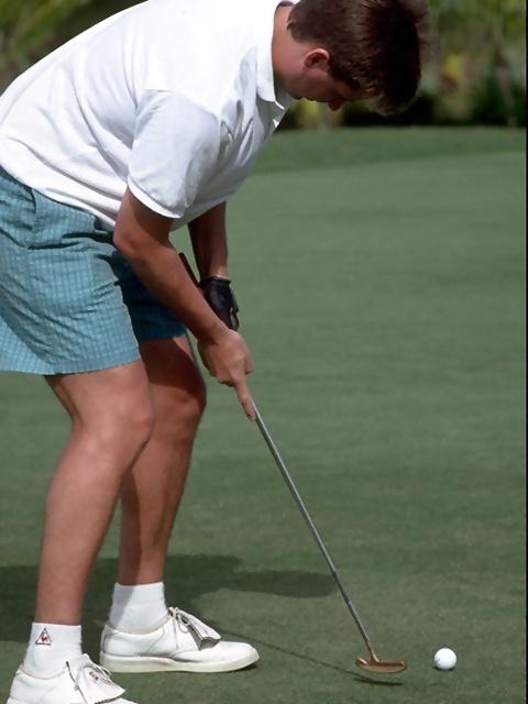 A man bending over to putt a golf ball : Free Stock Photo