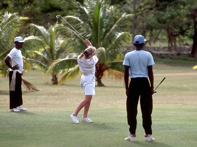 A woman swinging a golf club on tropical course : Free Stock Photo