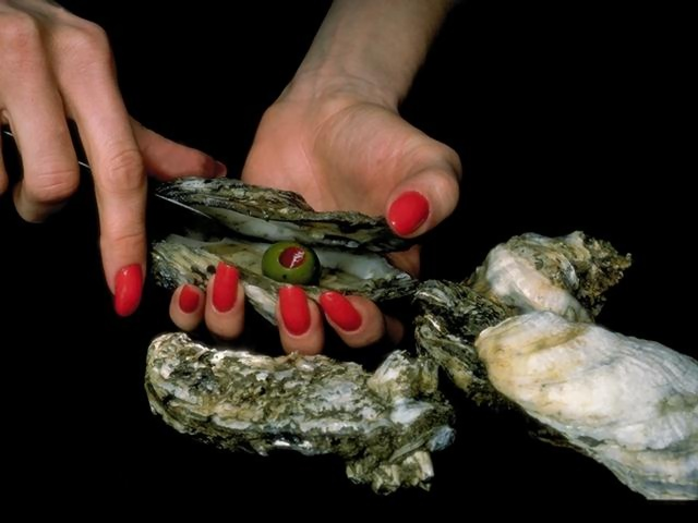 Close-up of a woman opening an oyster : Free Stock Photo