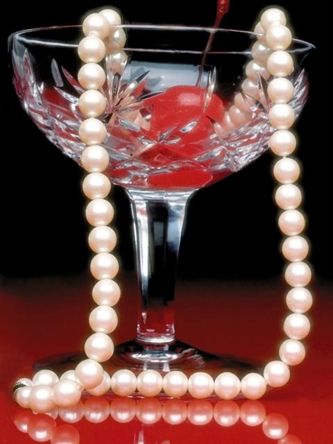 A glass with a cherry and string of pearls in it : Free Stock Photo