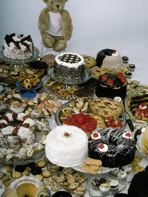 A display of cakes, cookies and other desserts and a teddy bear : Free Stock Photo