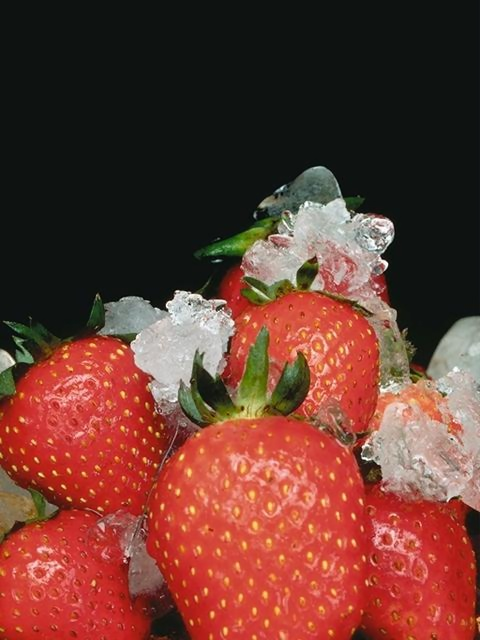 Frozen strawberries with ice on a black background : Free Stock Photo
