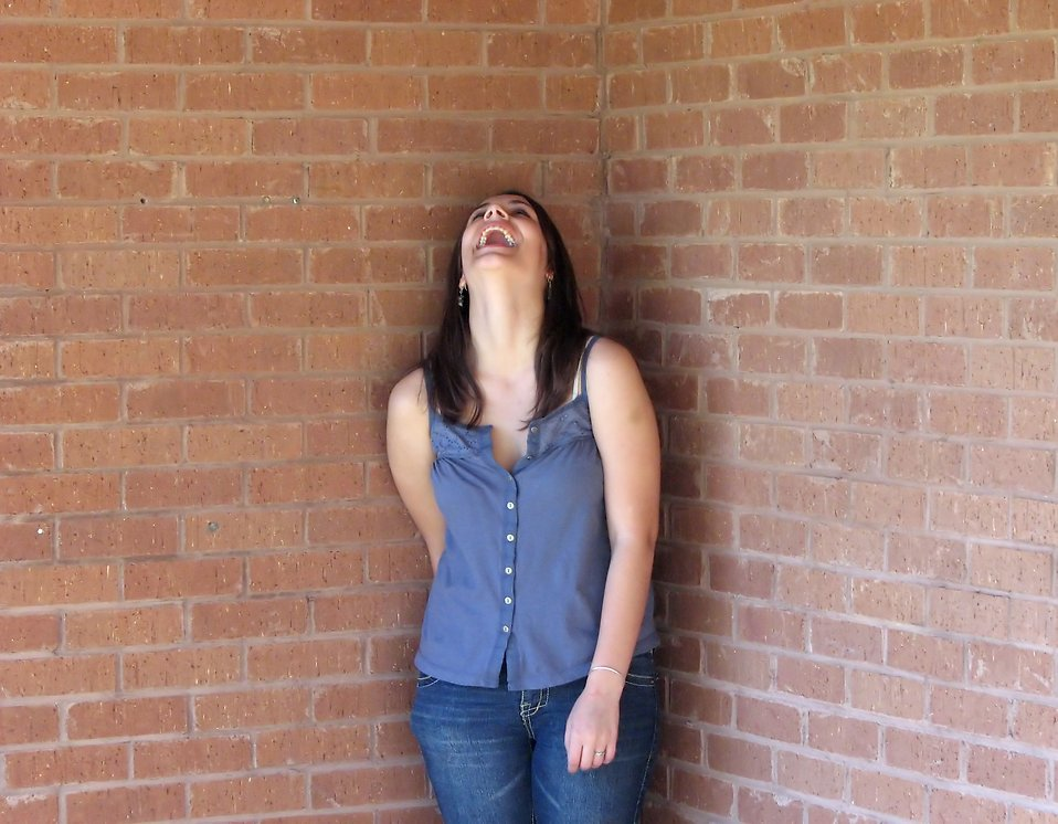 Free stock photo: Beautiful teen girl laughing in the corner of a brick wall ...