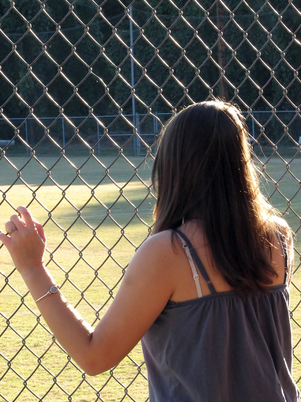 Beautiful teen girl looking through a chain link fence : Free Stock Photo