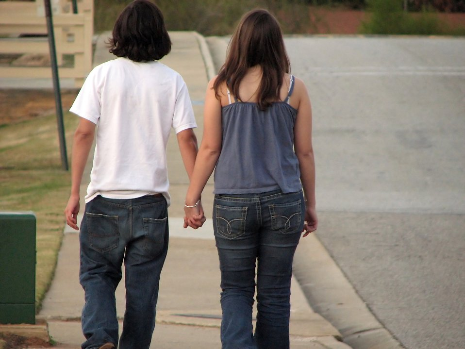Teen boy and girl holding hands walking on down the street.