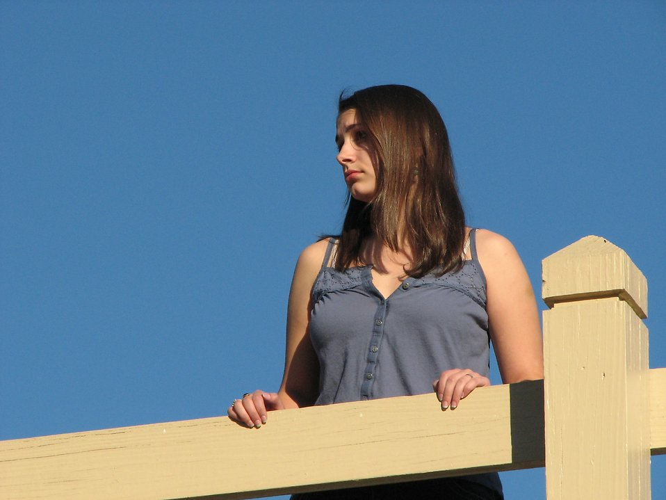 A beautiful teen girl looking over a wooden fence : Free Stock Photo