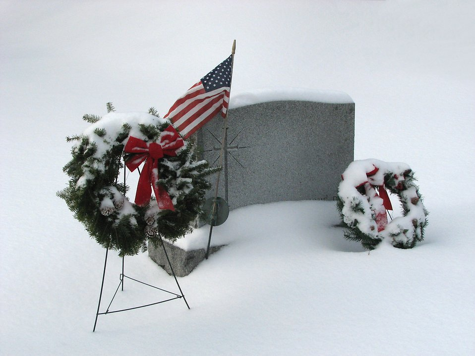 A blank snow covered tombstone with a US flag and wreaths : Free Stock Photo