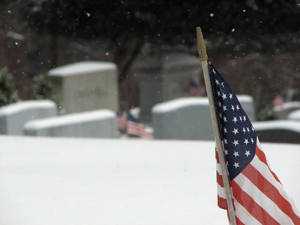 Closeup of a US flag in a snow coverd graveyard : Free Stock Photo