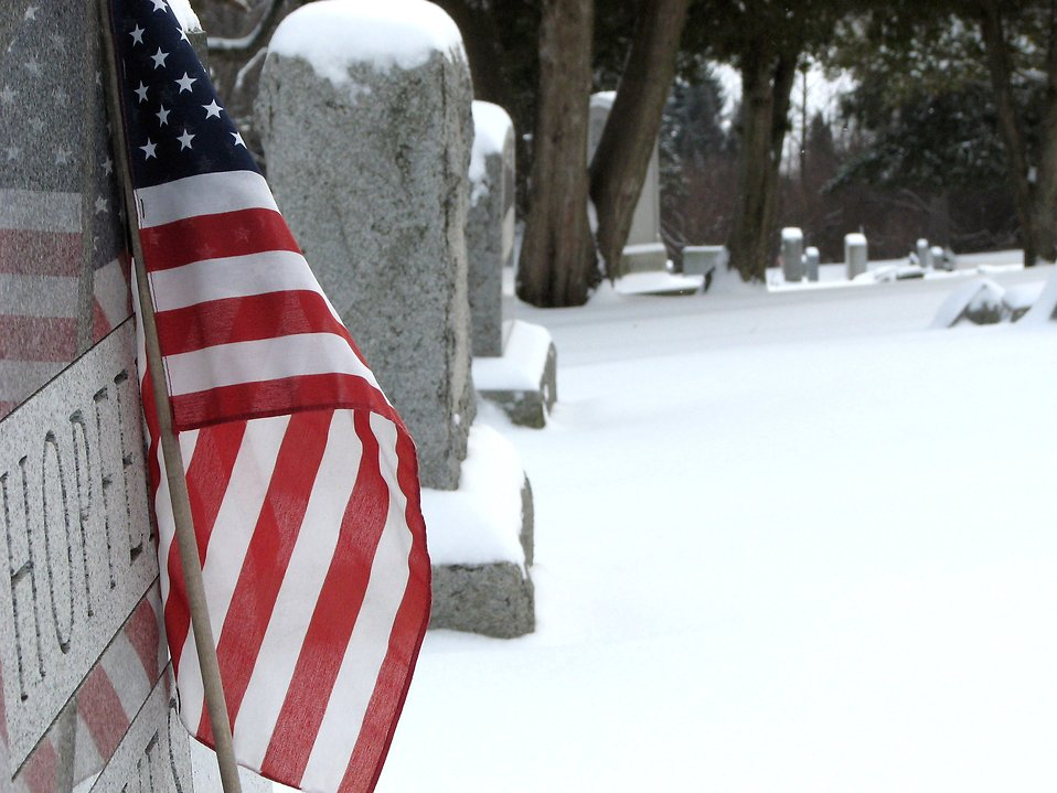 Closeup of a US flag and tombstone in a snow covered graveyard : Free Stock Photo