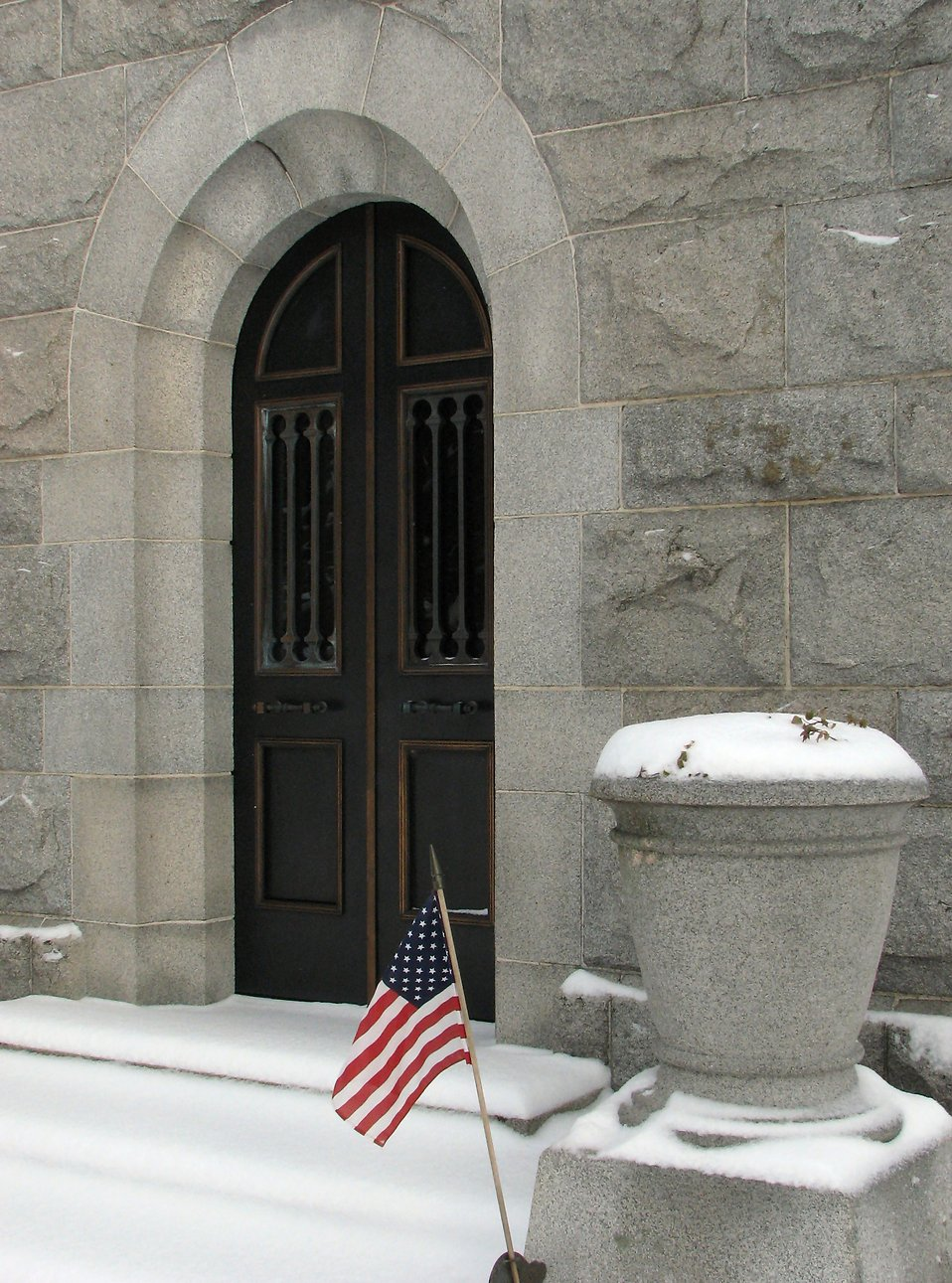 Entrance door of a small stone mausoleum with a US flag : Free Stock Photo