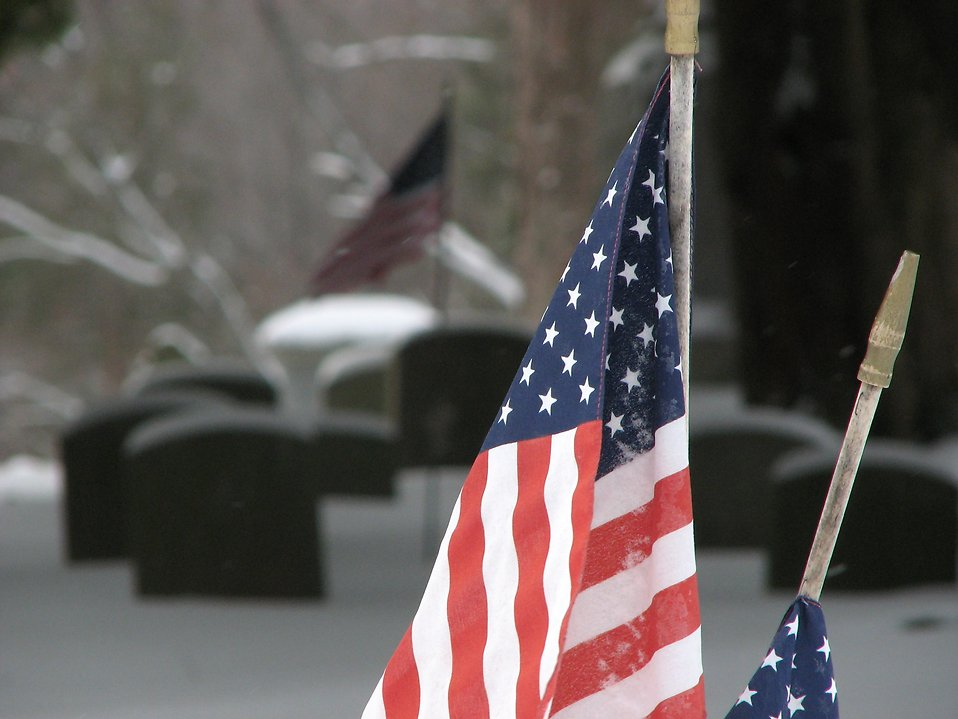 Closeup of US flags and tombstones in a snow covered graveyard : Free Stock Photo