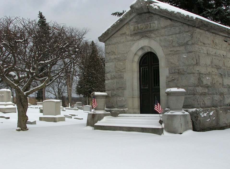 A small mausoleum with US flags in a snow covered graveyard : Free Stock Photo