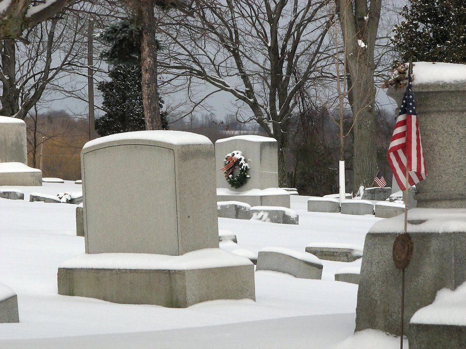A snow covered graveyard with wreaths and US flags : Free Stock Photo