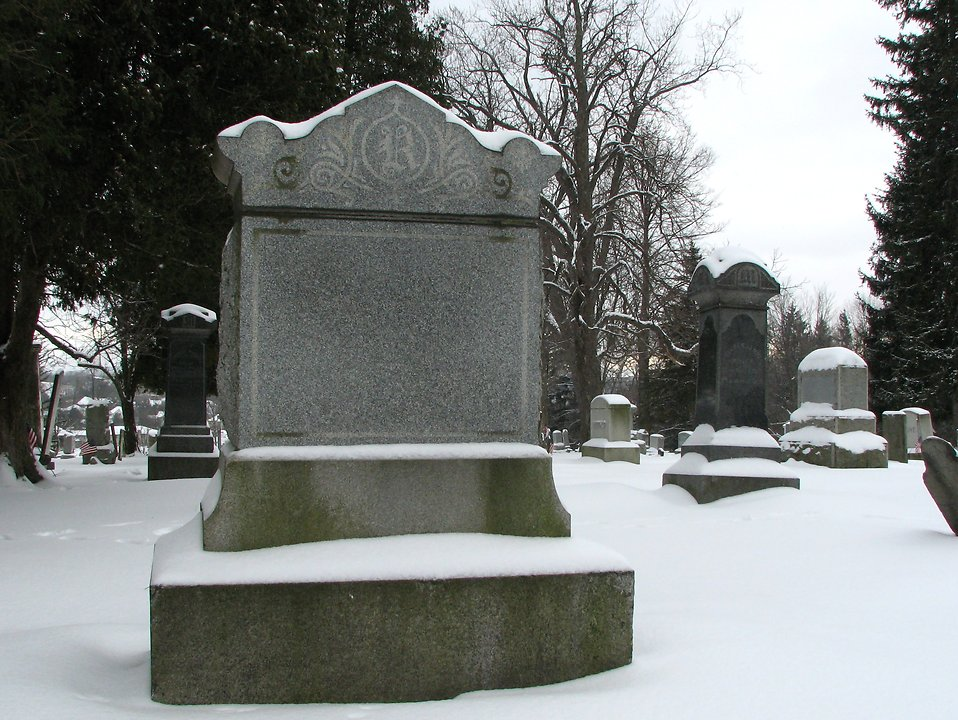 A blank tombstone in a snow covered graveyard : Free Stock Photo