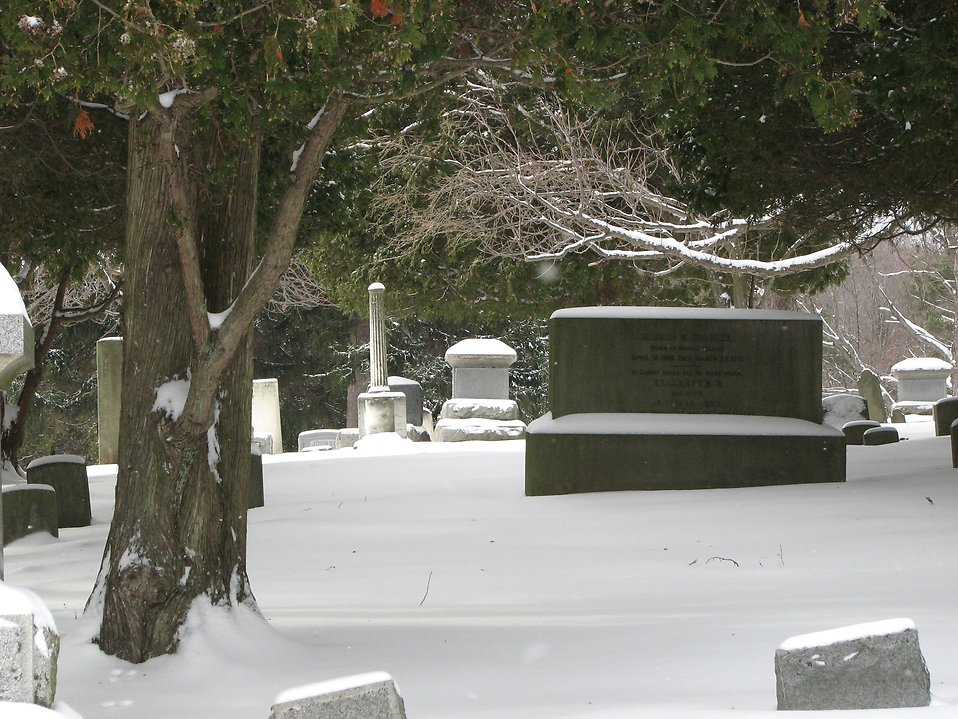 A snow covered tombstone in a graveyard.