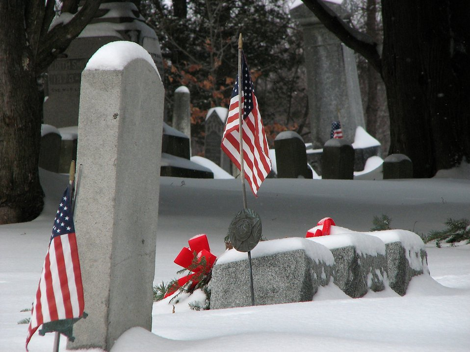 US flags and tombstones in a snow coverd graveyard : Free Stock Photo