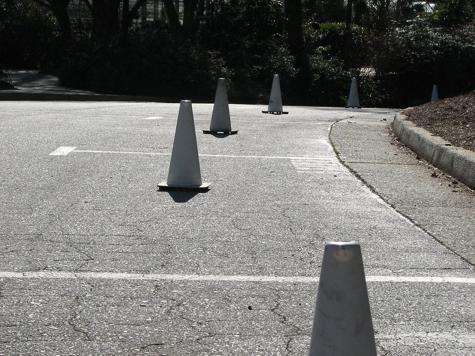 White construction pylons blocking empty parking spaces : Free Stock Photo
