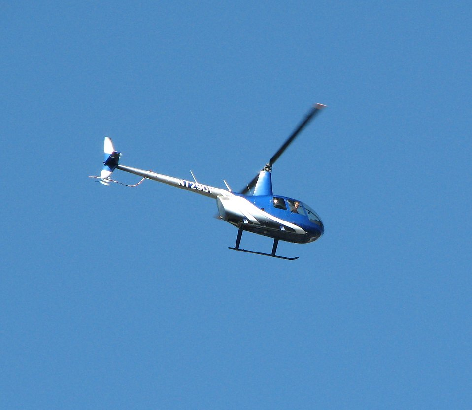 A small blue helicopter in the sky : Free Stock Photo