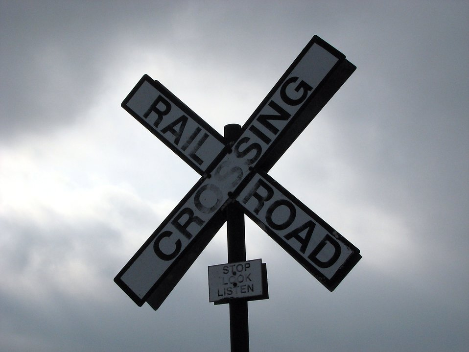 A railroad crossing sign in a cloudy sky : Free Stock Photo
