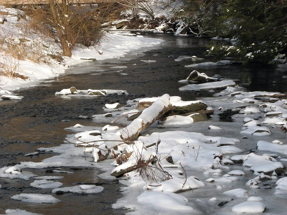 Snow and ice on the edge of a stream.