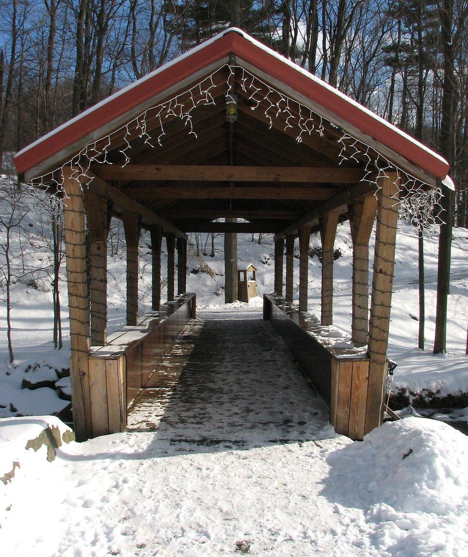 A snow covered bridge across a stream : Free Stock Photo