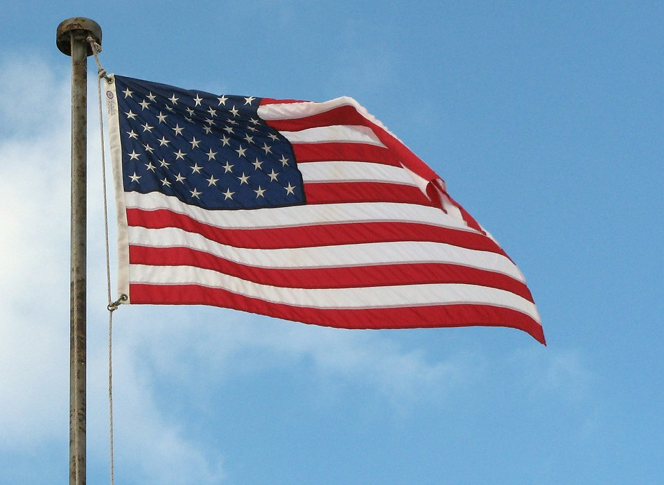 A US flag flying in a blue sky : Free Stock Photo