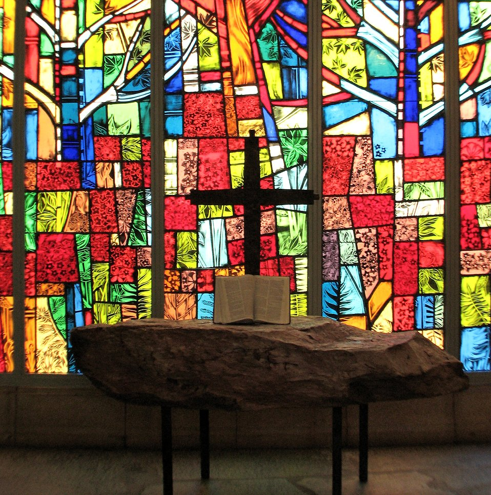 A small cross and a bible in front of a stained glass window.