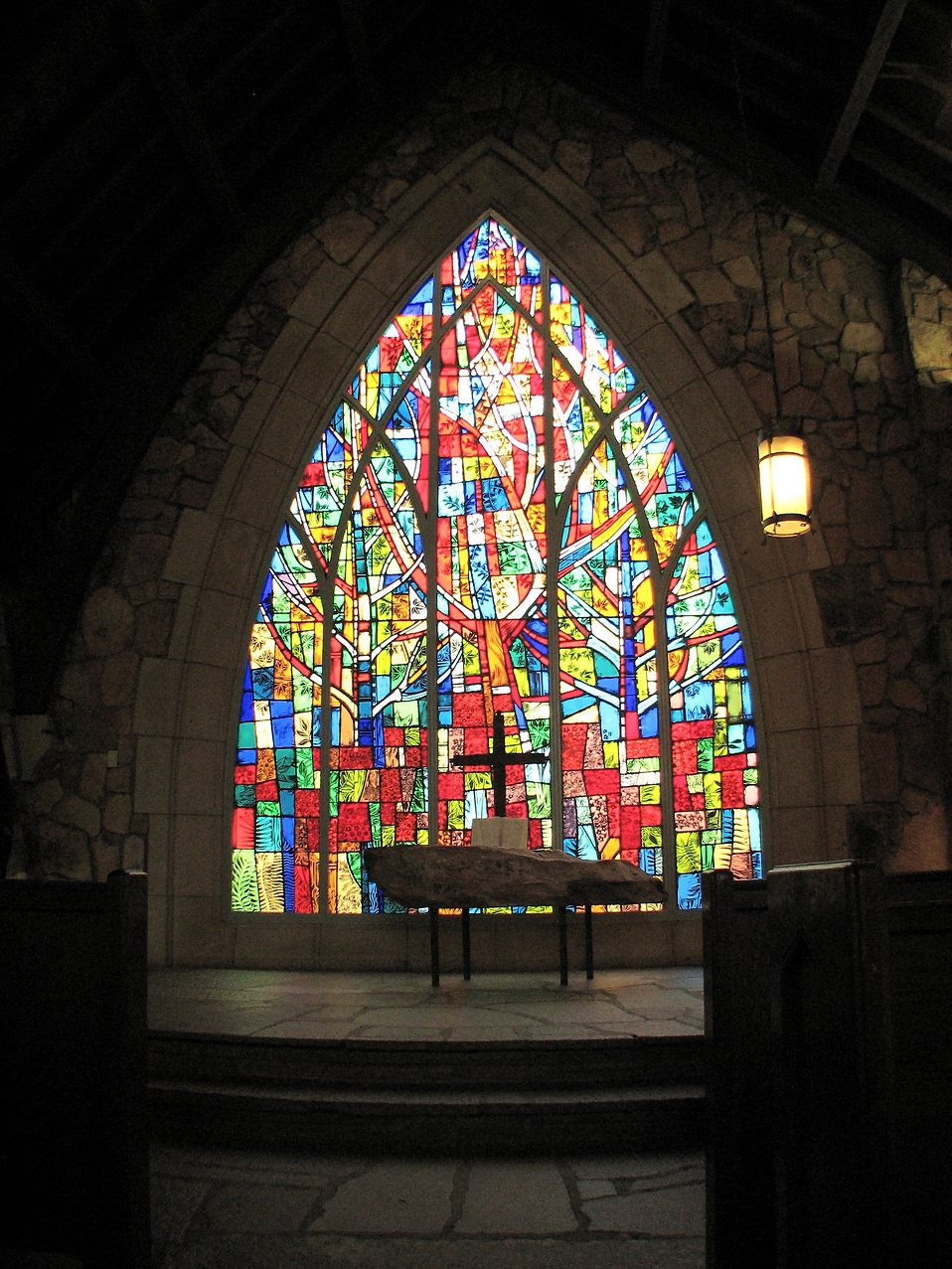 A small cross in front of a stained glass window.