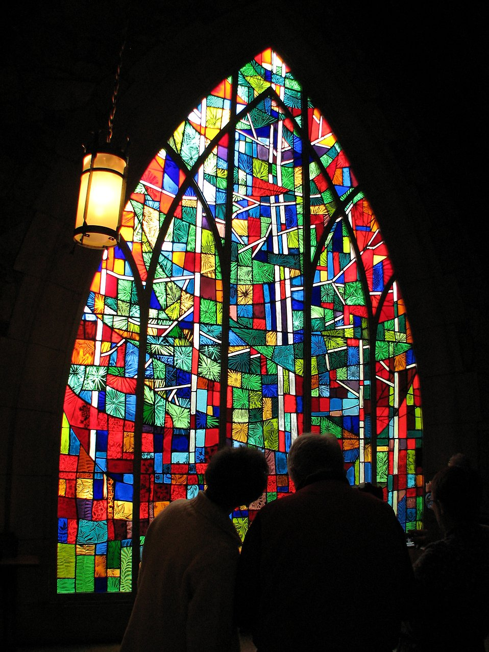 A couple standing in front of a stained glass window.