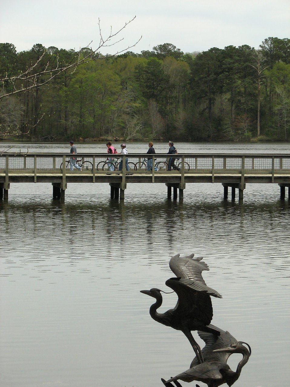People riding bikes across a bridge with a bird statue in the foreground : Free Stock Photo