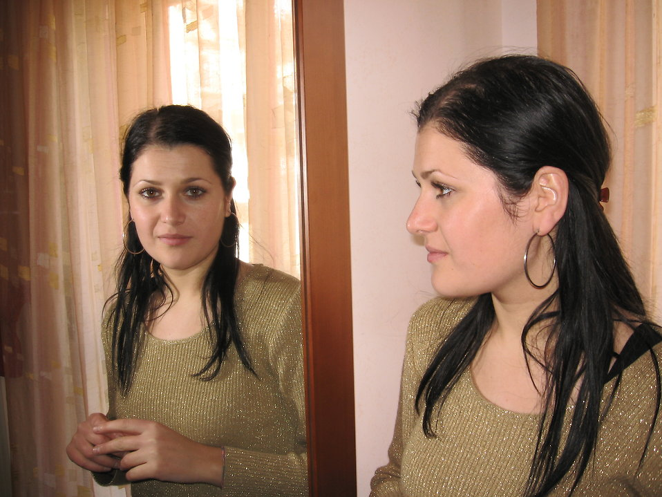 A young woman looking at herself in the mirror : Free Stock Photo