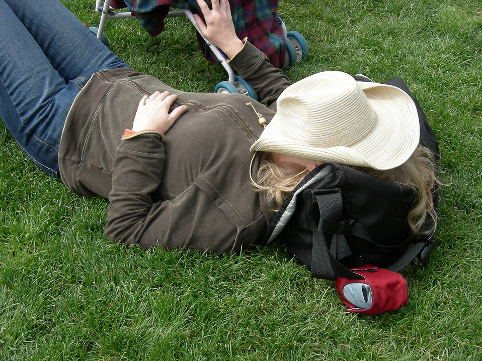 Woman resting on grass with hat over her face : Free Stock Photo