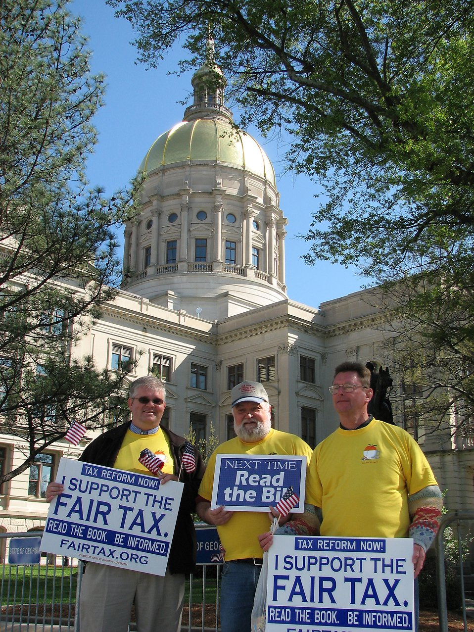 Men with protest signs in front of the State Capitol building at the 2009 tax day tea party in Atlanta, Georgia : Free Stock Photo