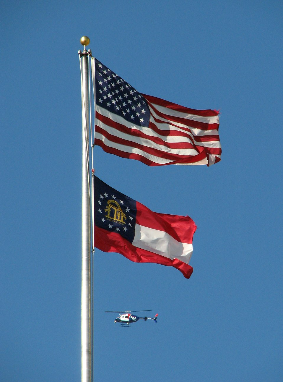 A helicopter flying by a US and Georgia flag : Free Stock Photo