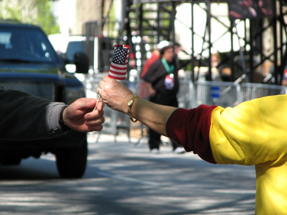 A woman handing a man a US flag at the 2009 tax day tea party in Atlanta, Georgia : Free Stock Photo