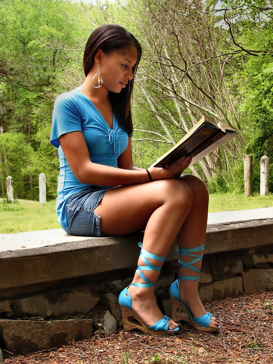 A beautiful African American teen girl reading a book on a stone wall outside : Free Stock Photo