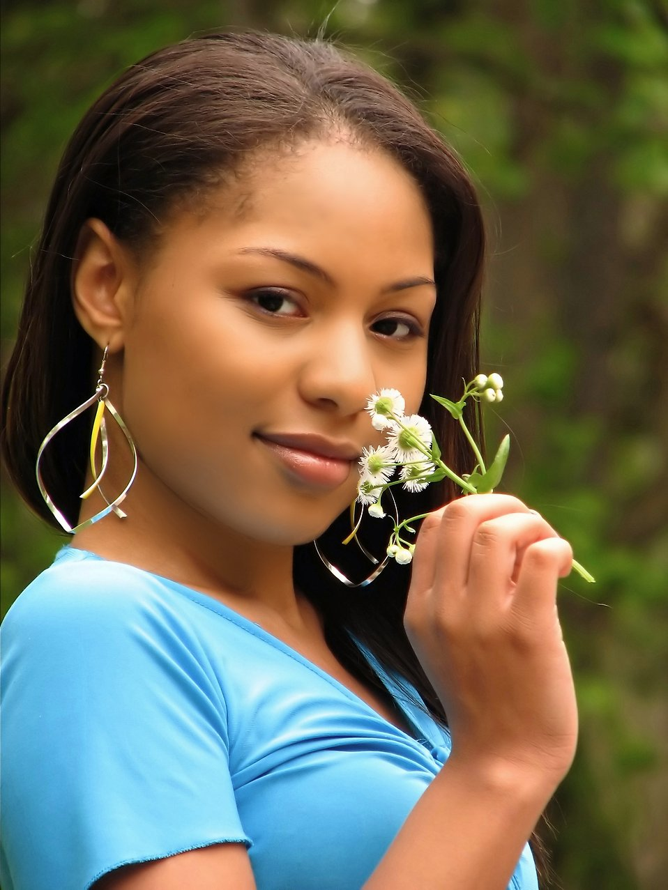 A beautiful African American teen girl smelling a flower : Free Stock Photo