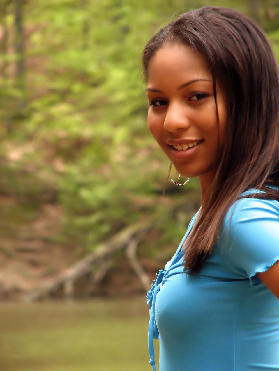 A beautiful African American teen girl posing in the woods near a lake : Free Stock Photo