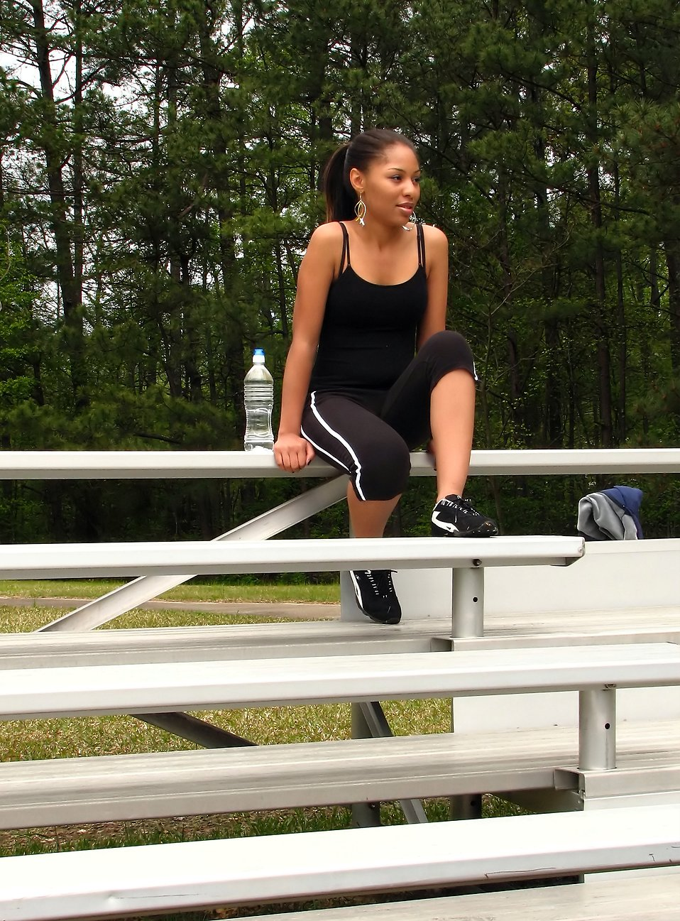 A beautiful African American teen girl sitting on bleachers with a bottle of water : Free Stock Photo