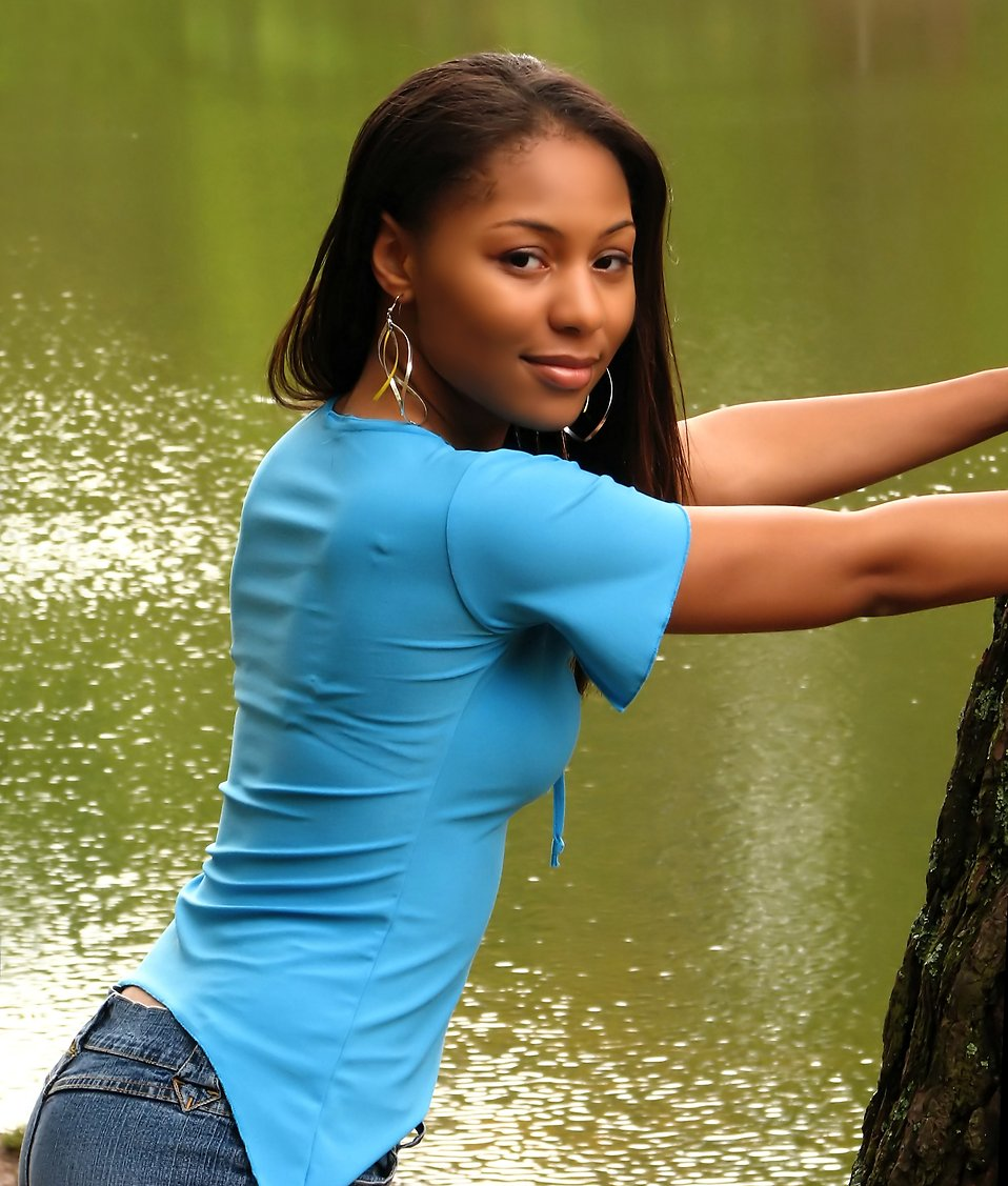 A beautiful African American teen girl posing against a tree near a lake : Free Stock Photo