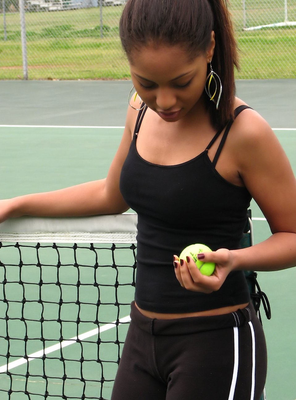A beautiful African American teen girl on an tennis court with a tennis ball : Free Stock Photo