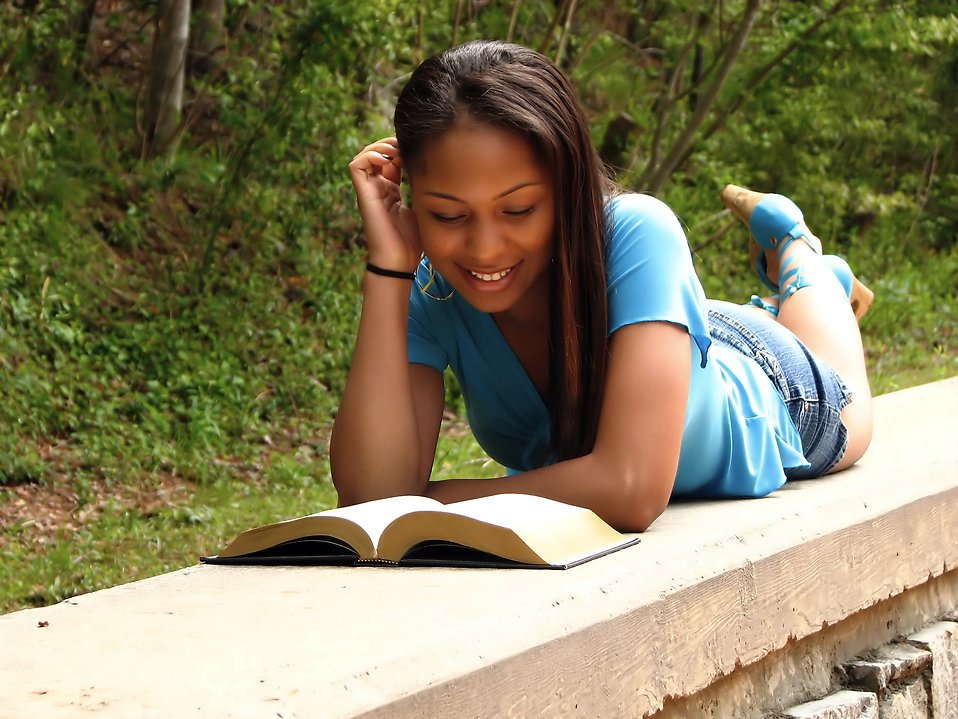 A beautiful African American teen girl reading a book on a stone wall in the woods : Free Stock Photo